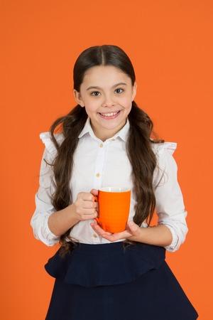 Girl kid school uniform orange background. Schoolgirl hold mug. School lunch. Drinking tea while break. Relaxing with drink. Tea break school. Children do not drink enough during school day.