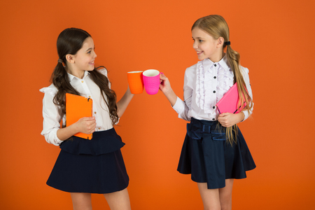 Drinking tea while break. School mates relaxing with drink. Enjoy being pupil. Girls kids school uniform orange background. Schoolgirl hold book or notepad and mug. School routine. Having break relax. 스톡 콘텐츠