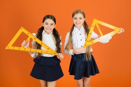 Education and school concept. School students learning geometry. Kids school uniform on orange background. Pupil cute girls with big rulers. Geometry school subject. Drawing with ruler chalkboard.