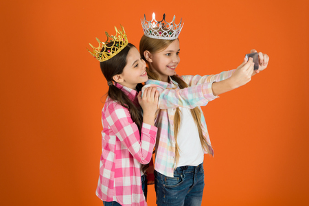 Demand more attention. Kids wear golden crowns symbol princess. Warning signs of spoiled child. Avoid raising spoiled kids. Girls taking selfie photo smartphone camera. Spoiled children concept.