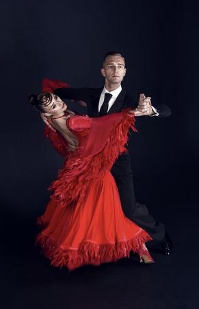 Tanzballsaalpaar im roten Kleid Tanzpose lokalisiert auf schwarzem Hintergrund. sinnliche professionelle Tänzer tanzen Walz, Tango, Slowfox und Quickstep.