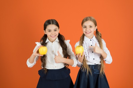 School lunch. Vitamin nutrition during school day. Boost student acceptance of fruit. Distributing free fresh fruit at school. Girls kids school uniform orange background. Schoolgirls eat apples.