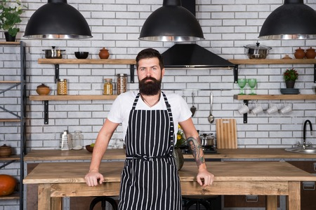He is a champion in the kitchen. Hipster in kitchen. Mature male. Bearded man cook. Bearded man in apron. Man chef cooking. Restaurant or cafe cook. Lunch time. Tired of cooking. Mature hipster. Zdjęcie Seryjne