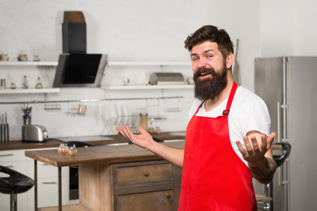 Welcome in the world of tastes. Hipster in kitchen. Restaurant or cafe cook. Bearded man in red apron. Mature male. Bearded man cook. Man chef cooking. Culinary expert. Perfect chef with neat look. Stock fotó