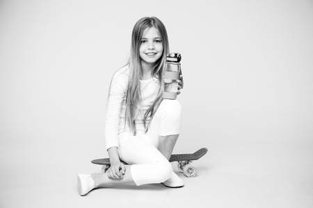Girl happy face holds with water bottle while sit penny board pink background. Kid girl care body hydration. Active leisure and water balance. Active and healthy kid drink water. Staying hydrated.