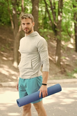 Practicing yoga. Sportsman carries yoga mat for outdoor practicing. Outdoor yoga concept. Man athlete on smiling face carries mat, going to stretching, nature background. Athlete with fitness tracker.