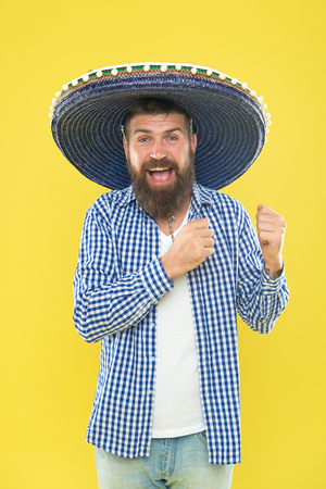 To your Mexican theme party. Hipster in wide brim hat. Mexican man wearing sombrero. Bearded man in mexican hat. Traditional fashion accessory for costume party. He is in love with mexican style. Foto de archivo