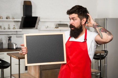 What to cook. urprise. This is what you need. Hipster in kitchen. Restaurant or cafe menu. Advertisement. Bearded man in red apron. Mature male. Bearded man cook. Man chef with board, copy space.