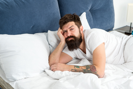 Man bearded hipster woke up too early and feels sleepy and tired. Early to get up. Keep you wide awake in the early morning hours. Insomnia and sleep problems. Reasons you are waking up too early.