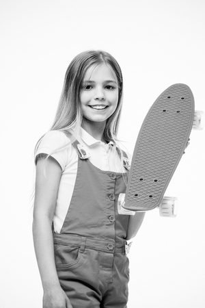 Little girl with penny board. Girl skater with penny skateboard. Little hipster skateboarder. Cute hipster. Enjoy vibes on penny board. Cruise till you can cruise no more. Banco de Imagens
