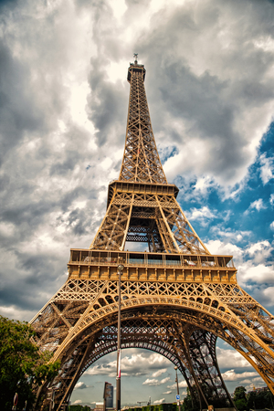 Eiffel Tower in Paris, France. Tower on cloudy sky. Architecture structure and design concept. Summer vacation in french capital.