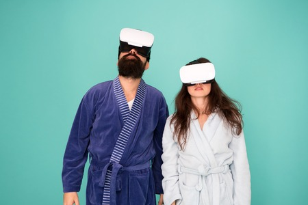 Bearded man and woman in robe. Couple in love. Family. Virtual reality and 3d. Love. modern family in vr glasses. 3d glasses. 3d technology. family couple in 3d glasses. vr headset. different reality. Фото со стока