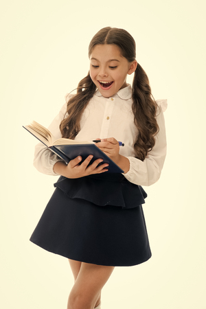 Little child with surprised look isolated on white. Schoolgirl with long hair hold book with pen. Girl in school uniform, back to school. Fashion genius. Open the book to life. back to school concept.