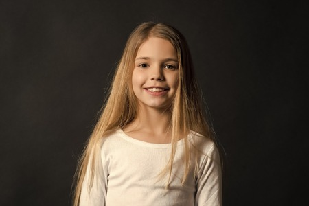 Kid model smiling with long healthy hair. Girl with smile on cute face on dark background. Beauty, look, hairstyle. Youth, skincare, health. Happy child, childhood concept.