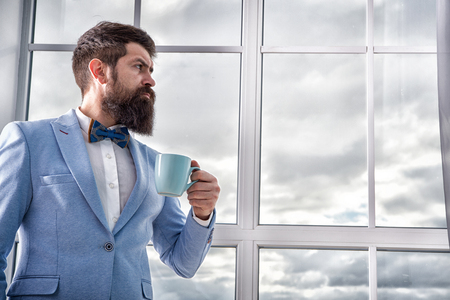 Beginning of great day. Important day in his life. Get ready. Enjoy every minute. Hipster in tuxedo with bow tie making sip of coffee. But first coffee. Man groom drinking coffee early in morning. Stock Photo