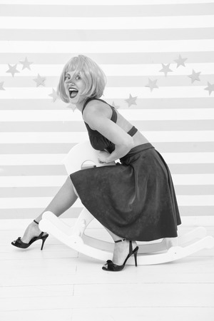 Comic and humorous concept. Woman playful cheerful mood having fun. Fun and entertainment. Girl wig rides swing little horse. Feel childish. Lady red or ginger wig blue dress rides rocking horse.