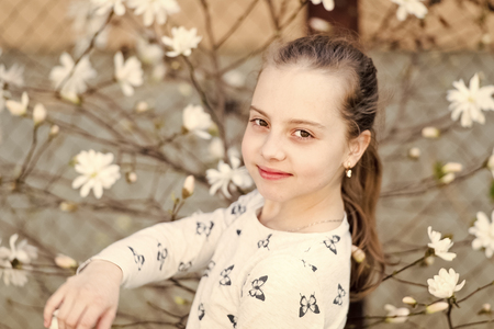 Beauty girl on floral blossom in spring. Beauty kid with fresh look and long hair.