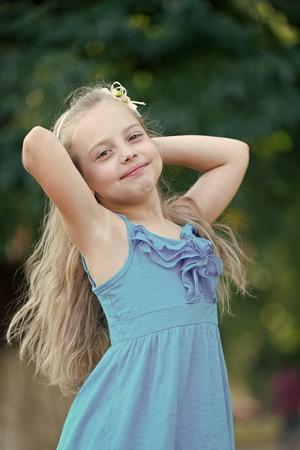 Sonrisa de niño con cabello largo y rubio, peinado. Niño, infancia, inocencia concepto de juventud.