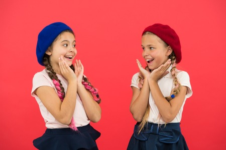 They are really cute. French style girls. Girls having the same hairstyle. Small children with long hair plaits. Fashion girls with tied hair into braids. Little kids wearing stylish french berets. Imagens