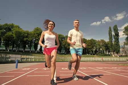 Runner on competition and future success. Man and woman sunny outdoor on blue sky. Couple running on arena track. Sport and healthy fitness. Coach and trainer at workout. Stok Fotoğraf