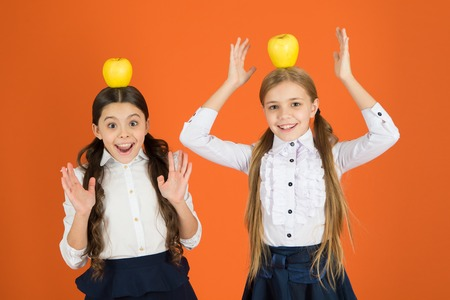 Let food be the medicine. Little girls taking school snack. Small girls eating natural vitamin food. Cute schoolgirls holding apples. School children with healthy snack. Fruits are high in vitamin.