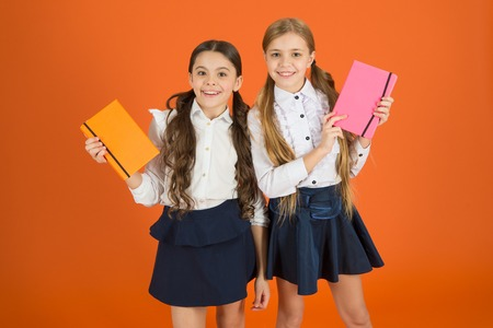 Smart and adorable. Cute schoolgirls holding lesson books. Little children with school diaries for making notes. School children learn reading books. Small girls classmates with workbooks for writing.