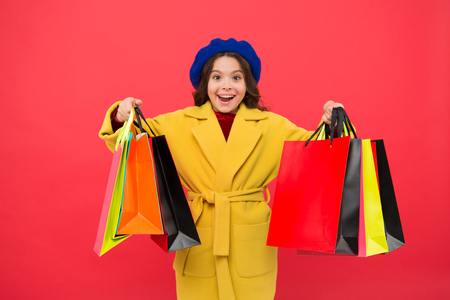 Fashionista adore shopping. Customer satisfaction. Prime time buy spring clothing. Obsessed with shopping. Girl cute kid hold shopping bags red background. Get discount shopping on birthday holiday. Stok Fotoğraf