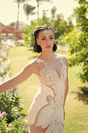 She is perfect. Girl attractive luxury dress accessory. Lady in luxury outfit walks exotic garden background. Woman make up hairstyle wears fashionable tight fitting dress with embroidery and pearls.