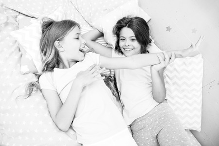 Slumber party concept. Girls just want to have fun. Invite friend for sleepover. Best friends forever. Consider theme slumber party. Slumber party timeless childhood tradition. Girls relaxing on bed. Stock Photo