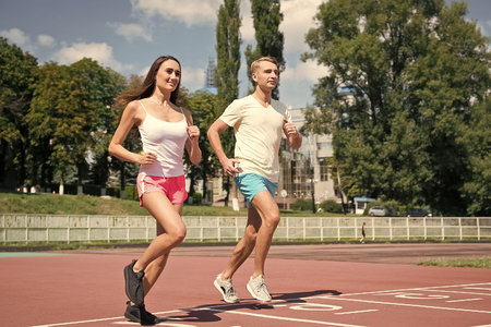 Woman and man run on stadium. Couple of runners on sunny outdoor. Activity and energy. Training and workout on fresh air. Sport health and wellness. Stok Fotoğraf