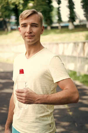 Thirsty man with water bottle on stadium. Sportsman with plastic bottle on sunny outdoor. Thirst and dehydration. Drinking water for health. Sport activity and energy.