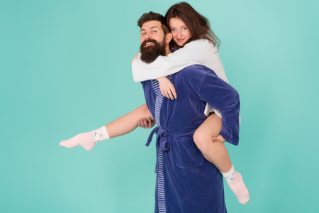 Lets stay at home and have fun. Couple in bathrobes having fun turquoise background. They always have fun together. Close relationship. Handsome young man giving his girlfriend piggyback ride.