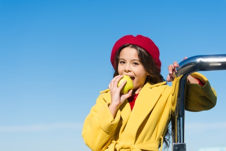 Vitamin nutrition. Cute child eating vitamin apple fruit on sunny day. Little girl biting into vitamin green apple. Small baby enjoy apple crop in autumn. Healthy vitamin snack for a kid.