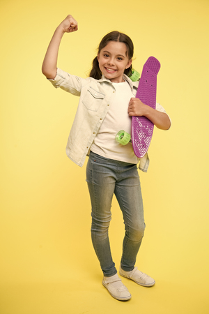 I can ride it. Kid girl happy holds penny board. Girl happy face carries penny board yellow background. Child learned ride penny board. Kid likes plastic skateboard shows power gesture. Girls power.