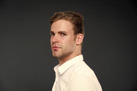 Confianza y masculinidad. Guy confiado en su apariencia. Hombre bien arreglado con fondo oscuro de cerdas y peinado. Macho cara estricta confiada de cerca. Chico guapo camisa blanca atractiva.