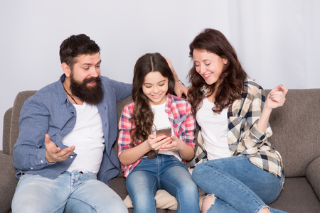 Child share news with mother and father. Little girl child use mobile phone. Happy family at home. Buy online. Child with childhood happiness. bearded man and woman with child. Family bonds.