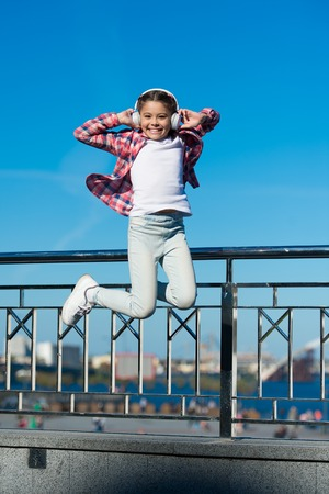 Like a rock star. Little girl jumping to music. Small happy child listening to music. Little child enjoying music playing in headphones. Cute music fan wearing wireless headset.