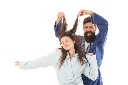 Good morning world. Go from flat to fluffy. happy bearded man play with hair of sleepy girl. family couple in robe. Love her hair. Hair health and care. I want to sleep. Morning sleepy couple.
