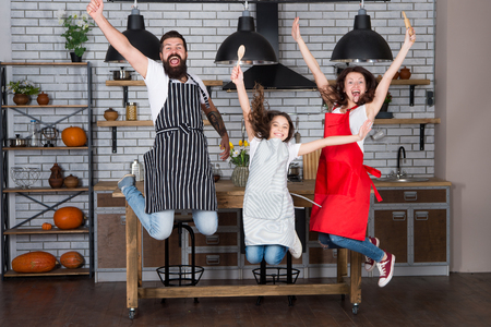 Happy family in kitchen. Enjoying morning. Father and daughter. Little girl with parents in apron. Mother and father with girl. Father, mother and child chef cooking. Mother and daughter in kitchen.
