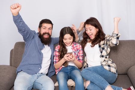 Family spend weekend together. Child little girl use smartphone with parents. Friendly family having fun together. Mom dad and busy daughter relaxing on couch. Family leisure. Parental advisory.