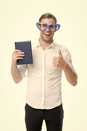 I love reading books. Man cute nerd in heart shaped glasses loves to read books. Guy holds book and shows thumbs up, isolated white. I always read at least few pages every day. My favorite book.