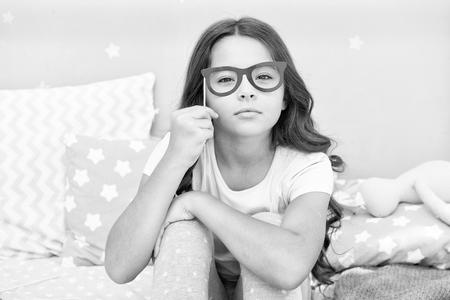 Geek accattivante. La bambina tiene gli occhiali finti sul viso. Bambina felice. Infanzia felice. Nei miei giorni d'infanzia. Archivio Fotografico