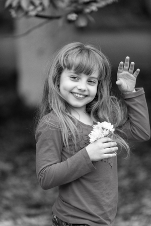 Child with sakura flowers, spring. Child smile with cherry blossom, beauty. black and white