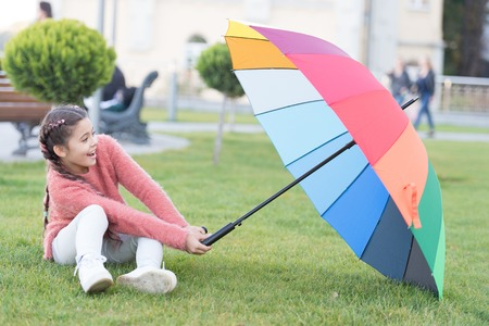 Colorful accessory for cheerful mood. Girl cheerful child long hair walking park with umbrella. Colorful accessory positive influence. Bright umbrella. Stay positive and optimistic. Optimistic child.