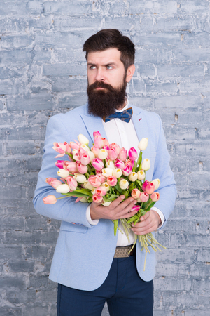 We take flowers personally. Spring gift. Bearded man hipster with flowers. Love. international holiday. Womens day. March 8. Bearded man with tulip spring bouquet. Spring time. enjoying spring.