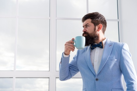 Man groom drinking coffee early in morning. Beginning of great day. Important day in his life. Get ready. Enjoy every minute. Hipster in tuxedo with bow tie making sip of coffee. But first coffee. Stock Photo