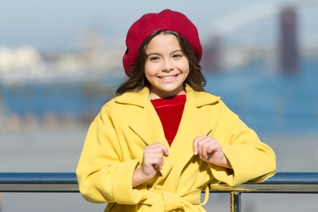 Girl adorable kid walk defocused background. Kid bright hat beret and warm coat. French style trend. Carefree relaxed walk. Health benefits of walking. Fashionable girl enjoy walk on sunny spring day.