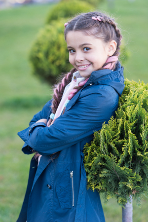 Fashionable hairstyle for kids. Girl small kid with fashionable braids hairstyle. Fashion trend. Salon and hair care. Girl cute smile face outdoors. Pleasant walk in park. Smile and joy. Cute smile.