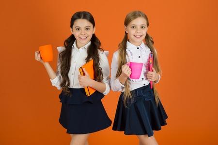 Mejorando su energía y estado de ánimo. Las niñas pequeñas disfrutan del desayuno escolar. Colegialas lindas sosteniendo tazas y libros. Niños pequeños bebiendo té o leche por la mañana. Niños en edad escolar desayunando por la mañana.