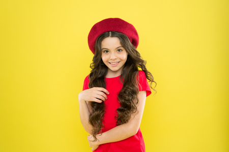 summer fashion beauty. happy girl with long curly hair in beret. childhood. hairdresser salon. shy little girl in french style hat. parisian child on yellow background. Joyful cute girl in red beret Stock Photo